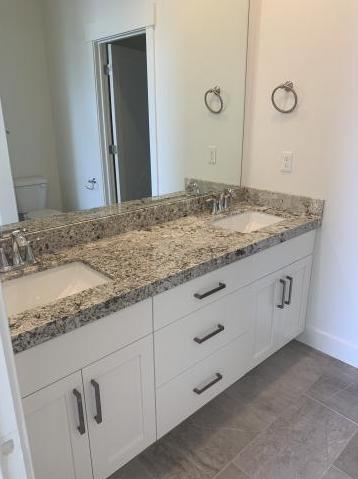 Bathroom vanity with white cabinets granite countertop and large mirror
