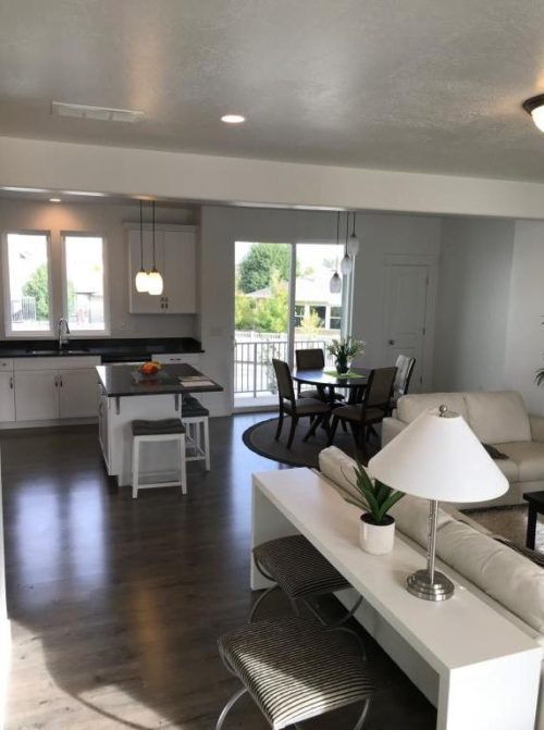 Staged living room and dining room with white couches and wood chairs and kitchen with white cabinets and black countertop