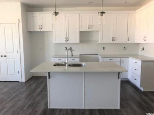 Light-filled kitchen with white cabinets and white quartz countertops and large in-island sink