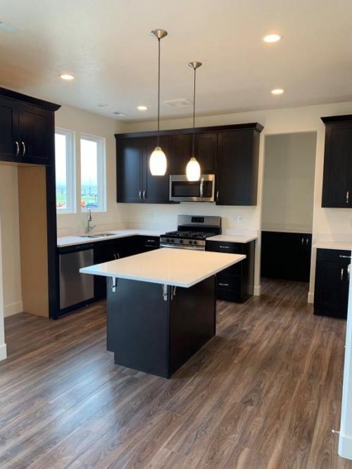 Gourmet kitchen with black cabinets and stainless steel hardware and white quartz countertops and stainless steel appliances