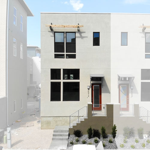 Front elevation of SoDa Row Lot 375 grey stucco building with black windows and a red door