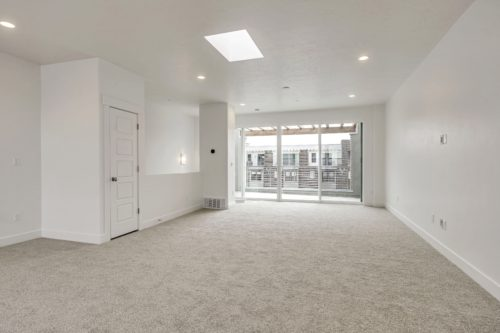 Light filled Sky Room with sky light and white walls and large sliding glass doors out to roof deck