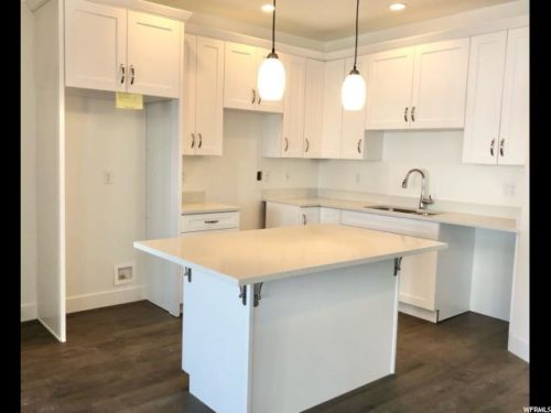 Light filled kitchen with tall white cabinets and white quartz countertops and wood laminate flooring