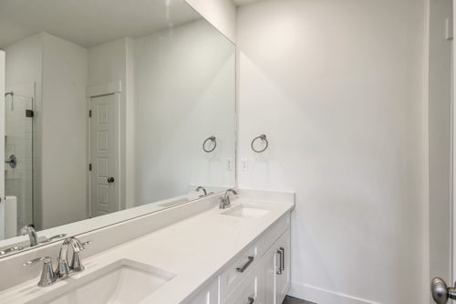 Double vanity master bathroom with white cabinets and white countertops and large mirror
