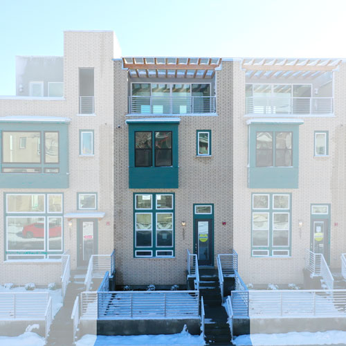 Front elevation of South Station Lot 242 with beige brick and teal trim and roof deck