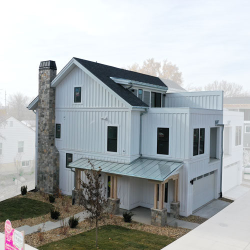 Side Elevation of Roof Gardens Lot 5 with vertical white hardi and rock fireplace chimney and covered porch with a roof deck