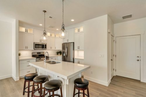 Light filled kitchen with island with white cabinets and white quartz countertops and stainless steel appliances
