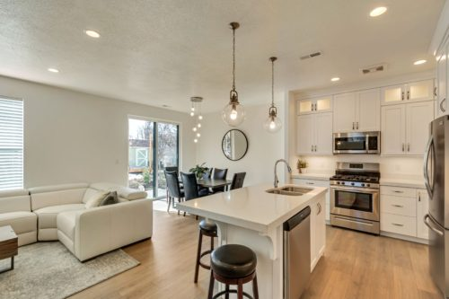 Light filled kitchen and dining with white cabinets and white quartz countertops and wood laminate floors