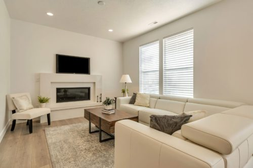Large windows and linear fireplace accent the white living room with white couches and wooden ottoman