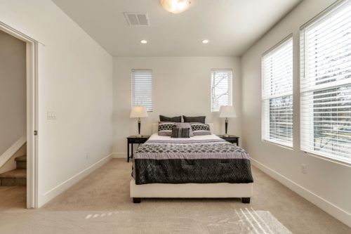Light filled master bedroom with grey bedding and white lamps