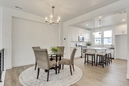 Light filled kitchen and dining room with white cabinets and countertops