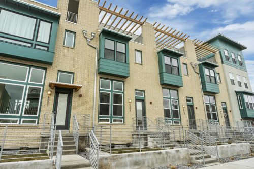 Exterior of South Station Lot 242 with Neutral Brick and Blue-Green Hardi Trim and Wooden Pergola