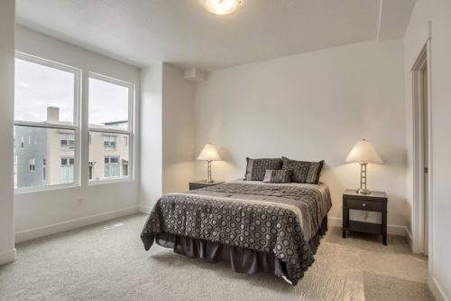 Large Master Bedroom with large windows and white walls and light carpet and grey geometric bedding