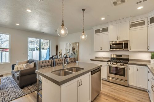 Light filled kitchen with white cabinets and grey quartz countertops opening to living room