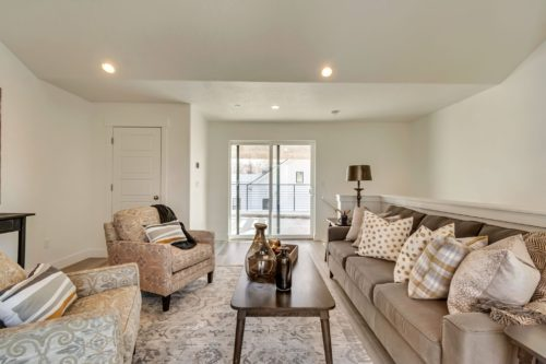 Light filled bonus room with grey couch and gold polka dot pillows opening up to roof deck