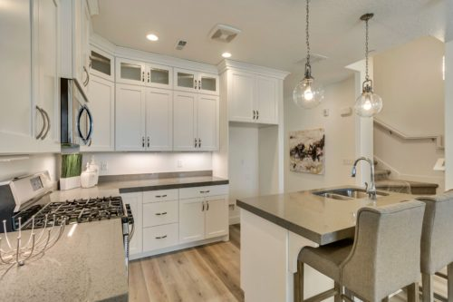 Light filled kitchen with white cabinets and grey quartz countertops and under cabinet lighting