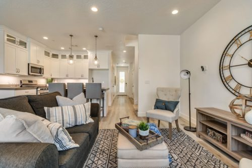 Light filled living room with grey couches facing entry way and kitchen