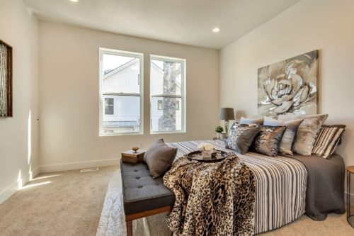 Light filled master bedroom with striped bedding and leopard print throw