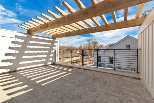 Private roof deck with metal railing and wood pergola