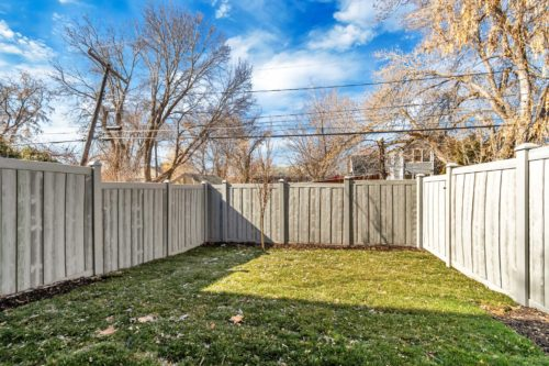 Private fenced yard with grass and grey fence