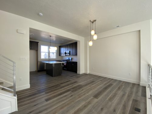 Lot 225 dining room facing the kitchen with dark floors and dark wood cabinets and white quartz countertop