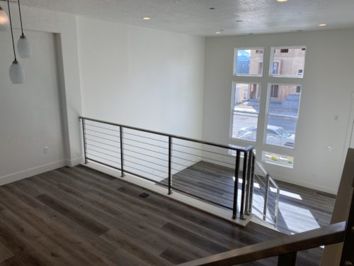 View from dining room of Lot 225 looking down into living room with metal railing and dark floors and large windows