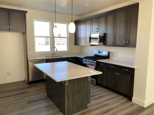 Lot 225 Kitchen with dark wood cabinets and white quartz countertops and stainless appliances