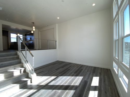 Lot 225 Living room with dark floors and white walls and metal railing