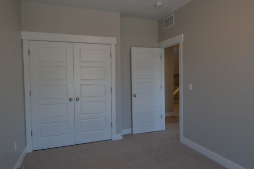 Roof Gardens Lot 4 2nd bedroom closet and doorway with grey walls and light carpet