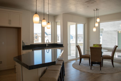 Lot 227 Light-filled dining room with pedant light fixtures and large windows and white cabinets and black granite countertops