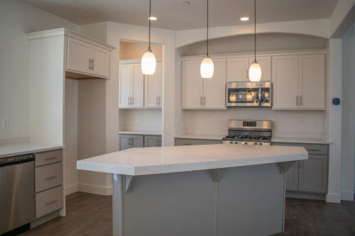 Lot 234 Kitchen with stainless steel appliances and white upper cabinets and grey lower cabinets and island and white quartz countertops and pedant lights and butler pantry