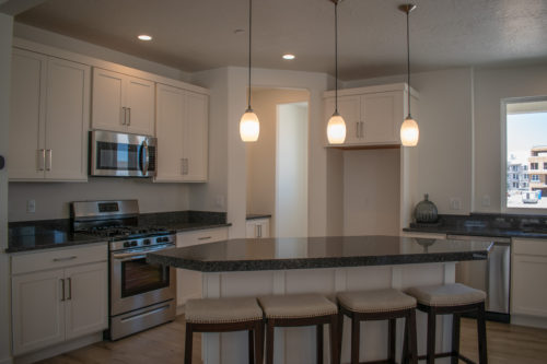 Lot 227 Kitchen with white cabinets and black granite countertops and pendant lights and stainless-steel appliances and butler pantry