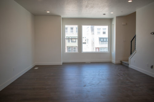 Lot 234 Living Room with huge picture window and white walls and brown flooring