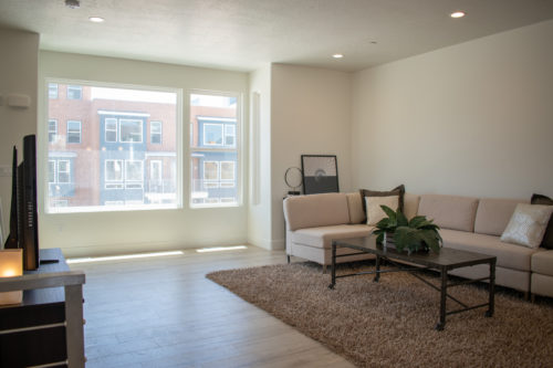Lot 227 Light-filled Living Room with large windows and white walls and light flooring and can lights