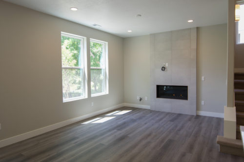 Roof Gardens Lot 4 Living Room with large windows and linear fireplace with tile surround and grey walls and brown flooring