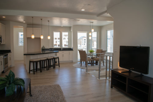 Lot 227 Light-filled Living room dining room and kitchen with light flooring and white walls and can lights