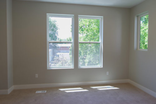 Roof Gardens Lot 4 Master bedroom with large windows and grey walls and light carpet