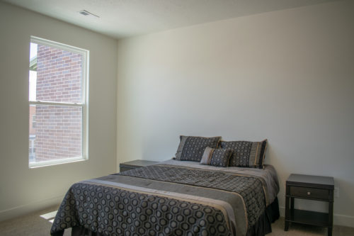 Lot 227 Master bedroom with large windows and white walls and grey bedding