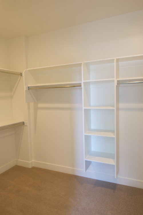 Roof Gardens Lot 4 Master closet with wooden built-in shelves and white walls