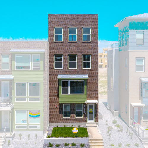 Front elevation of South Station Lot 227 red brick building with green hardi accents and grass yard
