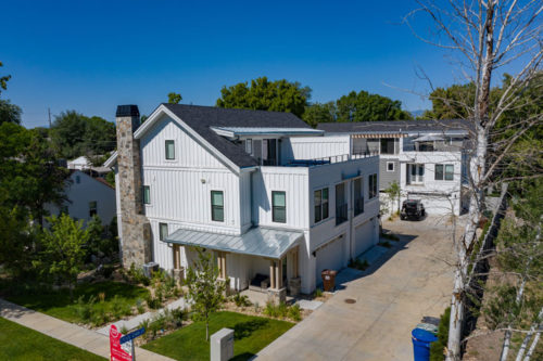 Roof Gardens Community with white farmhouse style townhomes and roof decks surrounded by trees in Salt Lake City