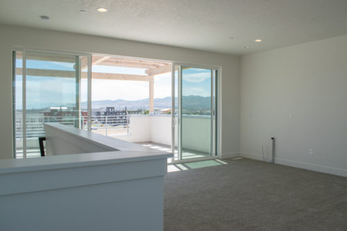 Lot 234 Sky Room and Roof Deck with large 16-foot glass sliding doors with white walls and light carpet and can lights